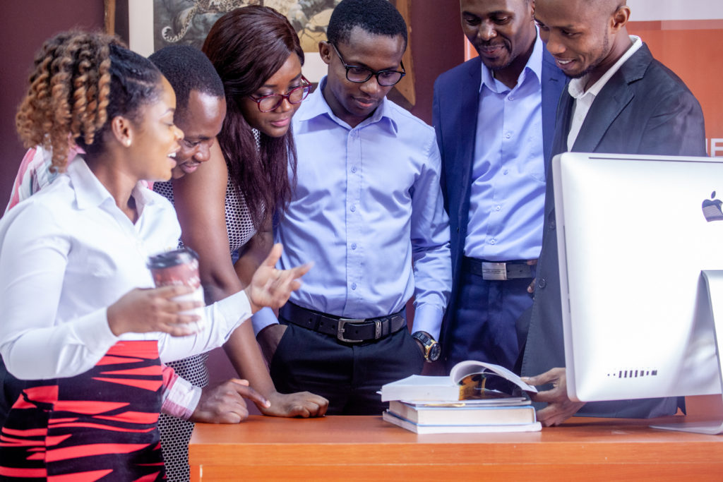 Six AmaliTech trainees surrounding a table that is covered with books and a computer